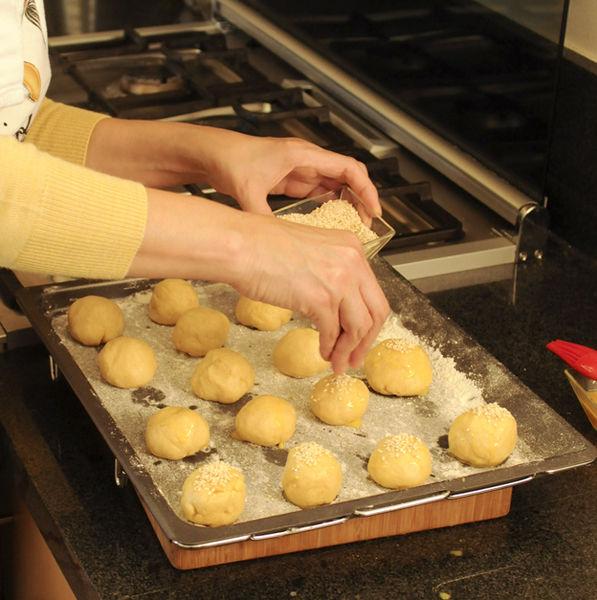 Barnizar las bolitas con el huevo batido, espolvorearlos con ajonjolí y hornear x 20 minutos hasta que estén doradas.