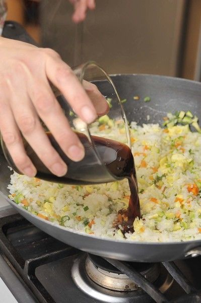 Mezclar el arroz con los huevos revueltos, agregar a la sartén de las verduras y calentar. Sazonar con la salsa de soya, el jengibre, la pimienta
