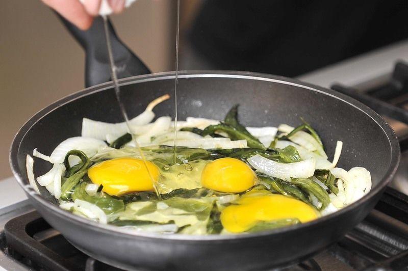 Agregar los huevos, dejar que se cuezan un poco y voltearlos con la pala de madera con un movimiento envolvente. Procurar no batirlos.