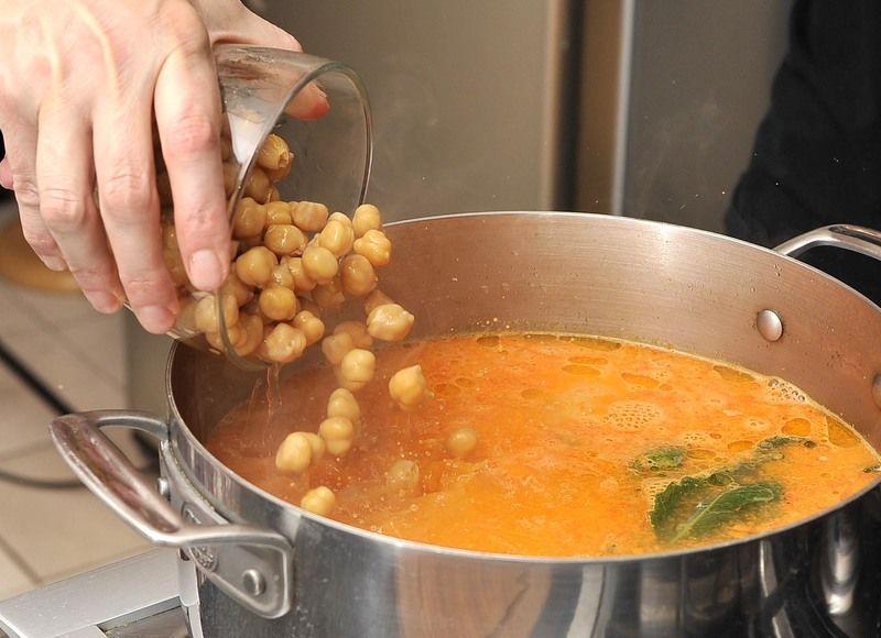 Añadir los garbanzos cocidos y escurridos junto con los chipotles enteros y el pollo desmenuzado, sazonar con sal al gusto y continuar cociendo 5 minutos para que se integren los sabores.