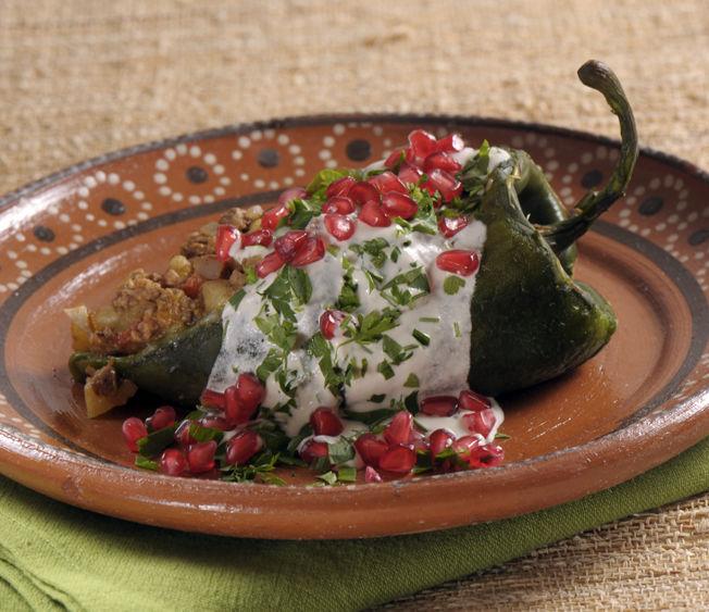 Para servir, calentar el relleno, rellenar los chiles, bañarlos con la nogada y decorar con toques rojos de granada y verdes de perejil picado.