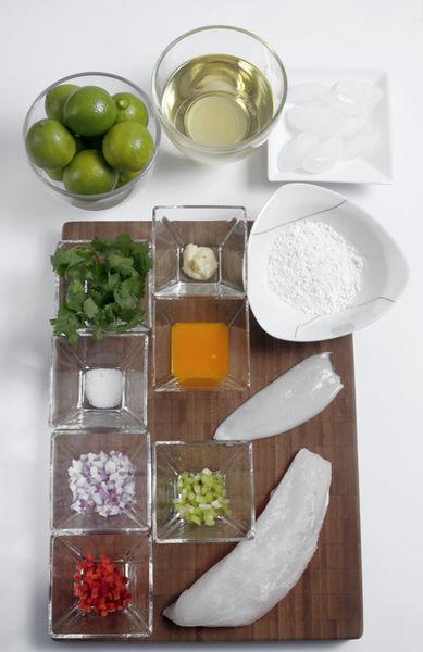 1 cucharada de apio 2 cucharadas de cebolla morada 1 cucharada de chile cuaresmeño 1 diente de ajo 1 cucharada de ají amarillo en pasta ¼ cucharadita de cilantro ½ taza de jugo de limón Sal al gusto 120 gramos de pescado blanco 50 gramos de calamar 2 cucharadas de harina 2 tazas de aceite vegetal 2 cubos de hielo