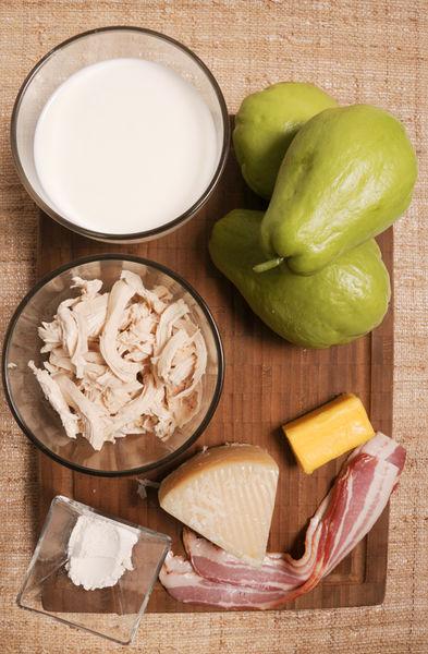 3 chayotes ½ barra de mantequilla (45 gramos) 4 rebanadas de tocino Sal al gusto Pimienta al gusto ¾ taza de pollo desmenuzado 1 cucharada de harina de trigo 1 ½ tazas de leche 200 gramos de queso manchego