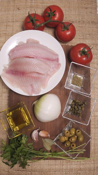½ cebolla 2 dientes de ajo 4 jitomates 2 hojas de laurel 4 filetes de pescado 2 cucharadas de perejil 12 aceitunas verdes 1 cucharada de alcaparras ½ cucharita de orégano seco Aceite de oliva extravirgen al gusto Sal al gusto