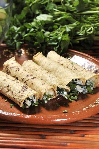 Calentar las tortillas sobre el comal. Rellenar con un poco las espinacas bien escurridas para que se les salga todo el líquido, espolvorear con cilantro picado, enrollar como tacos. Servir acompañados de salsa roja.