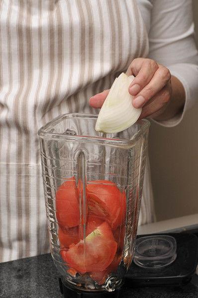 Para preparar la salsa roja, moler el jitomate junto con el trozo de cebolla y el diente de ajo en la licuadora.