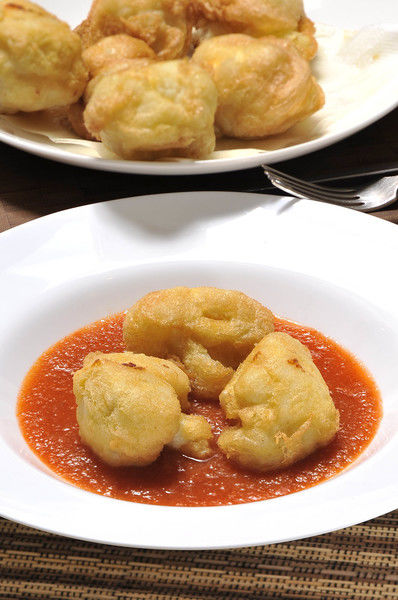Servir la salsa caliente en un plato hondo y colocar los trozos de coliflor capeada adentro.