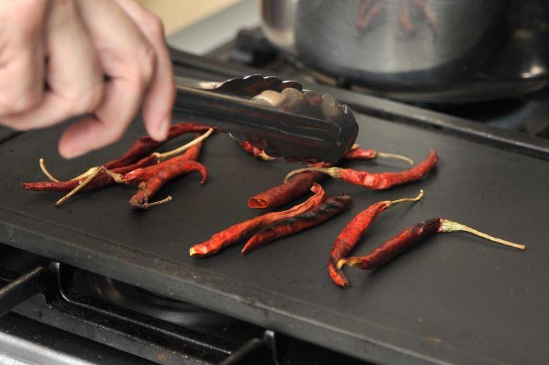 Poner a tostar los chiles sobre el comal, dando vuelta con una pinza hasta que se vean tostados pero no quemados.