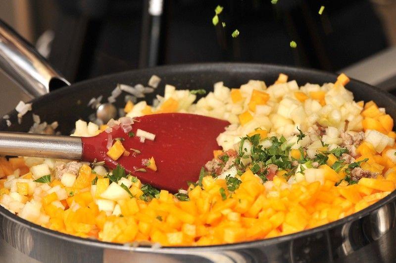 Agregar las manzanas, las peras, los duraznos, la mitad del perejil picado, dos cucharadas de jerez y las pasas, cocer durante 5 minutos. Añadir las almendras picadas y dejar 20 minutos más a la lumbre.