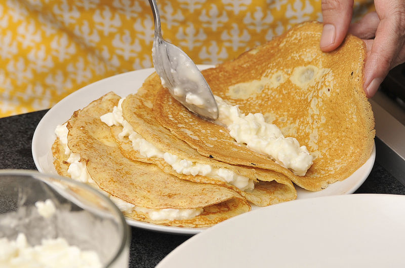 Rellenar cada crepa con un poco de queso cottage. Doblar en triángulo y colocar sobre el plato.