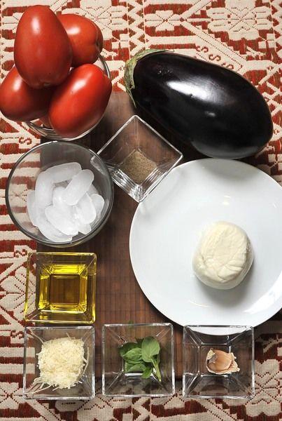 6 jitomates guaje 1 diente de ajo 6 hojas Albahaca fresca 1 berenjena grande 250 g de queso Mozzarella 2 cucharadas de queso parmesano Aceite de oliva Sal Pimienta Hielo