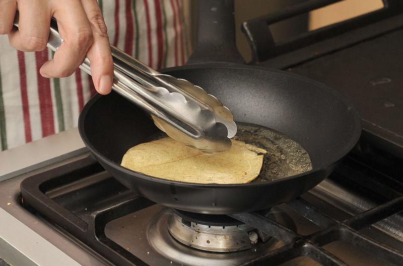 Poner a calentar aceite en un sartén pequeño. Con ayuda de una pinza, pasar las tortillas brevemente por el aceite para que se suavicen. Reservar sobre un plato.