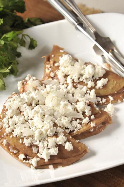Servir cuatro enfirjoladas calientes en cada plato, como desayuno o cena, espolvoreadas con más queso fresco encima.