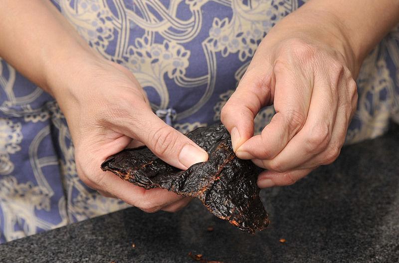 Lavar muy bien las pechugas de pollo y ponerlas a hervir en agua con un trozo de cebolla y sal, tapado y a fuego lento durante 40 minutos hasta que estén bien cocidas. Poner a hervir los chiles anchos sin rabo en agua durante 5 minutos.