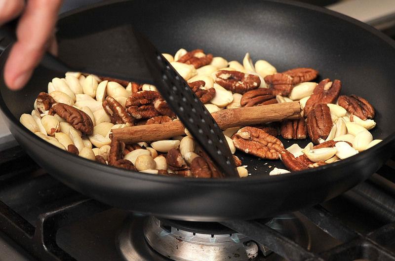 En un sartén abierto, calentar el ajo, los cacahuates, la nuez, la canela, la pimienta y los clavos de olor, meneando constantemente con una pala de madera para que no se quemen porque pueden dar un sabor amargo.