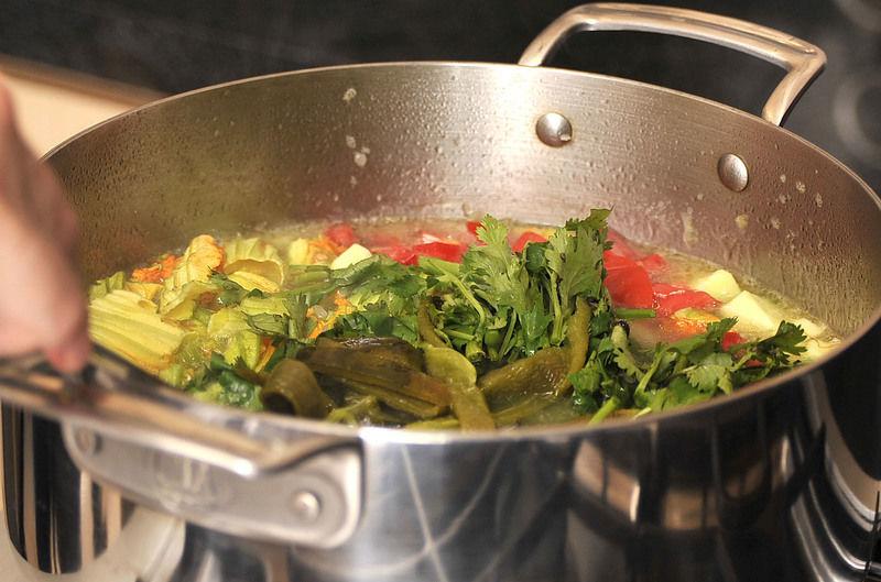 Agregar el jitomate, el cilantro y el chile poblano, rectificar la sazón y dejar hervir cinco minutos más.