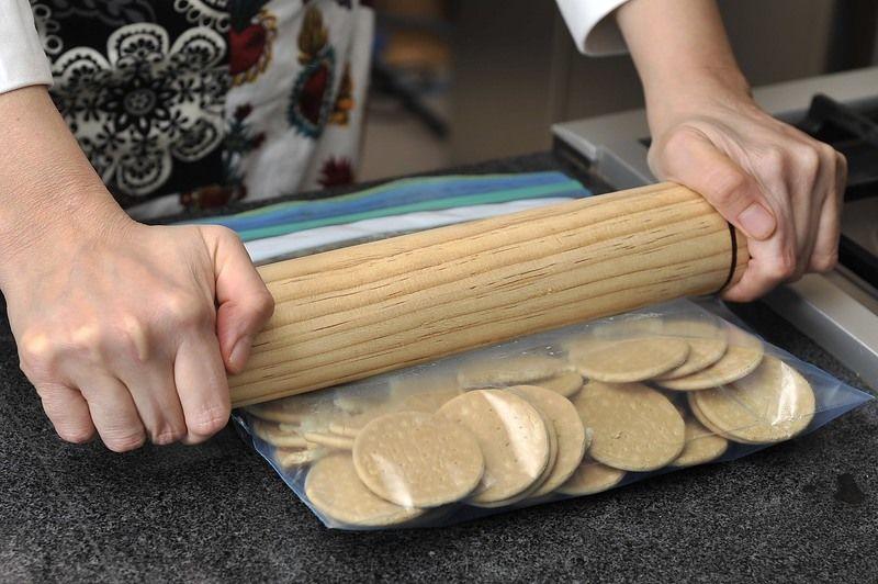 Para prepara la base, colocar las galletas de canela o Marías en una bolsa de plástico resellable y aplanar con el rodillo hasta que queden bien molidas.
