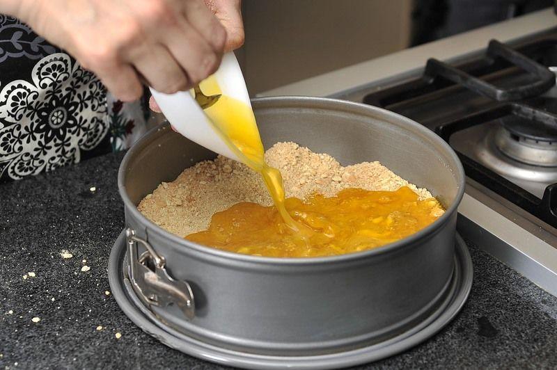 Agregar la mantequilla derretida y mezclar bien. Aplanar bien toda la mezcla sobre la base del molde.