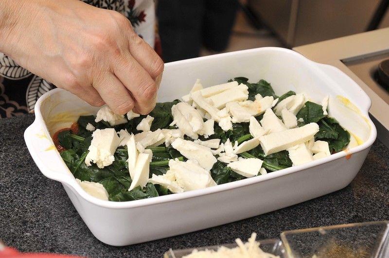 Sobre ellas una capa de espinacas, después otra de salsa, luego queso mozzarella desmenuzado.