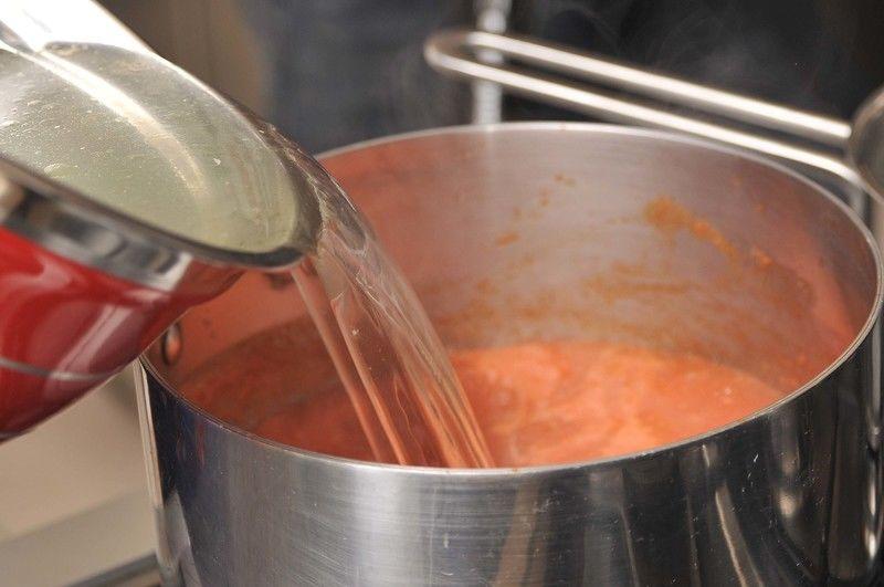 Agregar el caldo de pollo y la rama de epazote, sazonar con sal y calentar hasta que suelte el hervor.