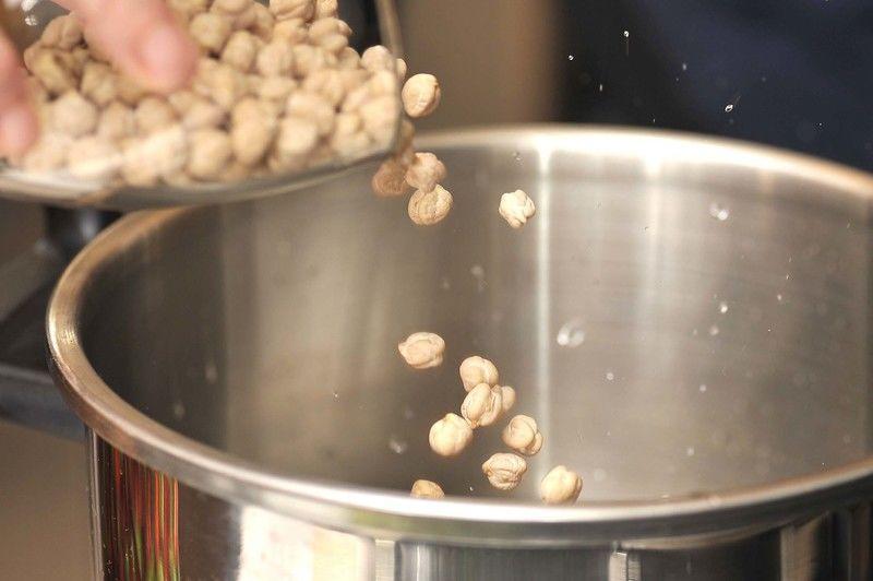 Colocar los garbanzos en suficiente agua dentro de una olla de presión. Sellar la olla, poner a fuego alto hasta que comience a silbar. Bajar la lumbre, continuar cociendo 30 minutos. Apagar el fuego y dejar enfriar por completo antes de desfogar la válvula y abrir.