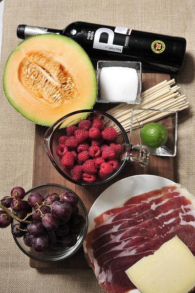 Ingredientes: 1 botella de mas petit pares balta 2 tazas de frambuesa palitos de madera al gusto 1 racimo de uva morada sin semilla 300 gramos de queso manchego 100 gramos de jamón serrano 1/2 pieza de melón 1 pieza de limón 1/4 taza de azúcar blanca