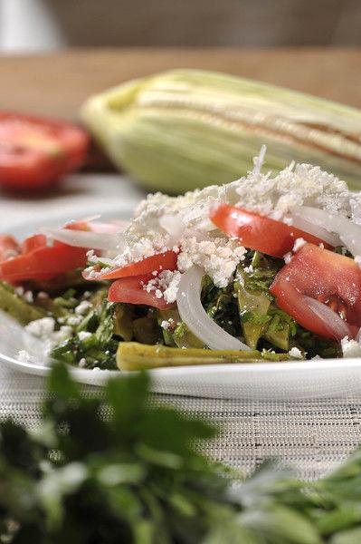 Colocar los nopales en un Platón, decorar con jitomate, cebolla y queso. Acompañar con totopos.