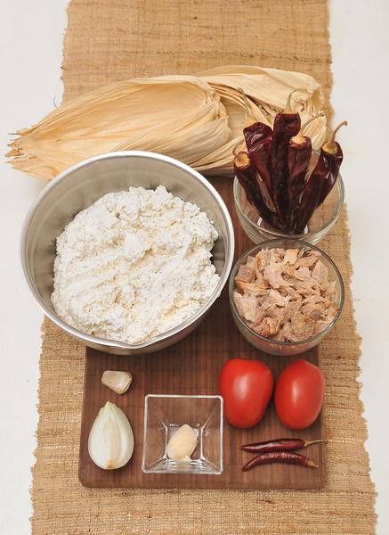 2 jitomates guaje ¼ de cebolla 1 diente de ajo 5 chiles guajillo 2 chile de árbol 1 ½ tazas de pierna desmenuzada Sal al gusto 1 cucharadita de manteca de puerco 500 gramos de masa para tamal Hojas de elote para tamal