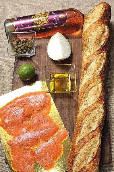 250 gramos de salmón ahumado 2 cucharadas de alcaparras ¼ de cebolla 1 limón Aceite de oliva Pan bolillo o baguette