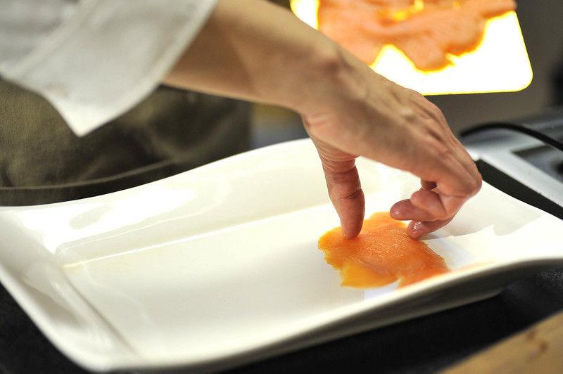 Picar finamente la cebolla. En un plato extendido disponer delgadas rebanadas de salmón ahumado.