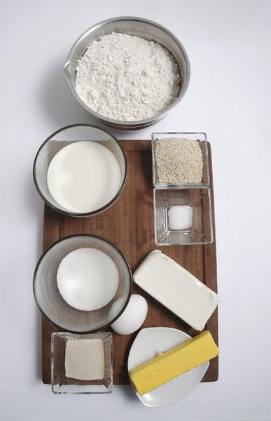 4 tazas de harina de trigo 15 gramos de levadura ½ cucharadita de sal ½ taza de azúcar 1 barra de mantequilla (90 gramos) 1 taza de leche 1 barra de Queso crema (190 gramos) 1 huevo Ajonjolí para espolvorear Papel plástico adherente