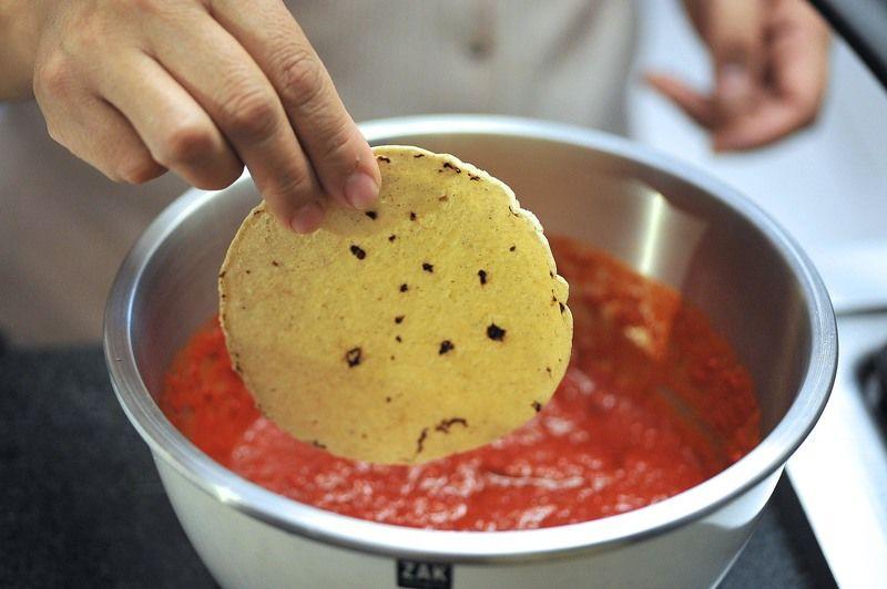 Calentar un poco de aceite en una sartén abierta. Sumergir las tortillas una por una en la salsa de chile.