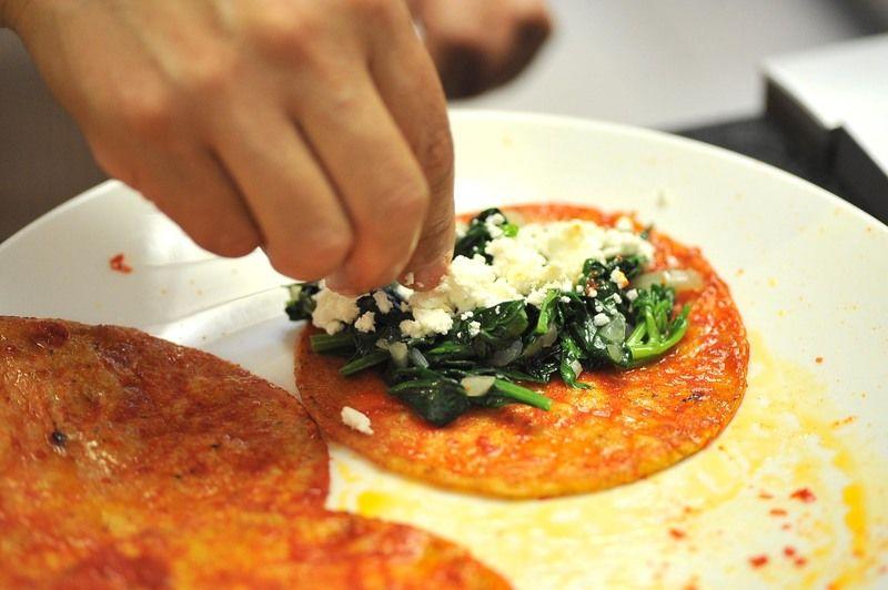 Añadir un poco queso fresco, envolver en forma de enchiladas. Colocar 5 enchiladas en cada plato. Espolvorear con queso fresco.