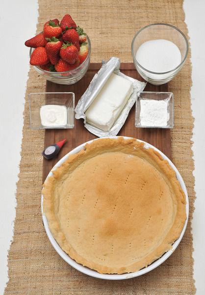 1 taza de Azúcar blanca 3 cucharadas de Maicena 1 gota de Colorante rojo vegetal 1 pieza de Costra de pay cocida 1/2 kilogramo de Fresa 3 cucharitas de Crema ácida 190 gramos de Queso crema