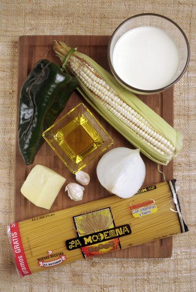 200 gramos de espagueti 1 chile poblano 1 elote ¼ de cebolla 2 dientes de ajo 1 taza de crema 100 gramos de queso chihuahua Aceite de oliva Sal al gusto