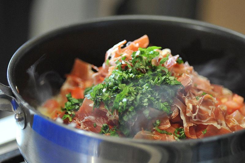 Añadir el jamón serrano, el jitomate y la albahaca picados. Sazonar con sal y continuar cociendo durante 10 minutos.