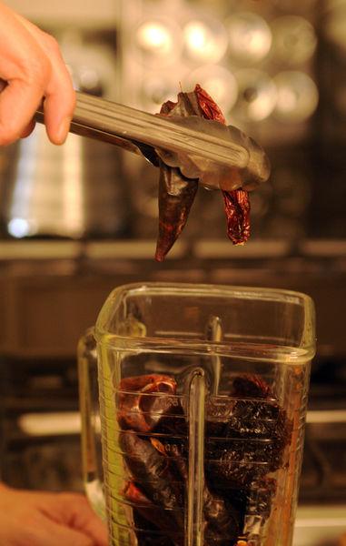 Asar sobre el comal los chiles anchos, guajillos, morita y cascabel, dando vuelta con unas pinzas hasta que estén tostados. Retirar a cada uno el rabo y las semillas, si se quiere menos picoso retirar las venas. Colocar un poco de agua en el vaso de la licuadora y moler todos los chiles con los ajos, pimienta, orégano, canela, jengibre y un poco de sal de mar.
