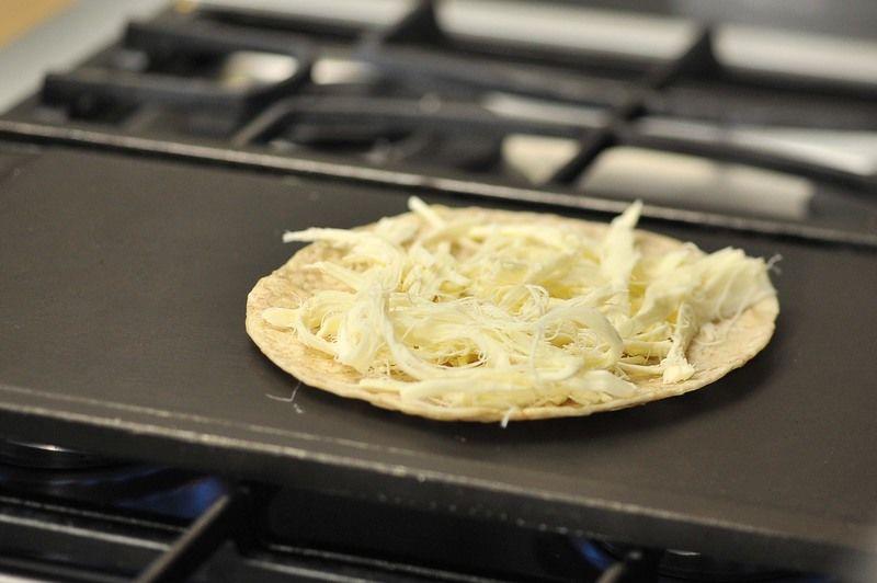 Añadir la mitad del queso desmenuzado sobre la tortilla.