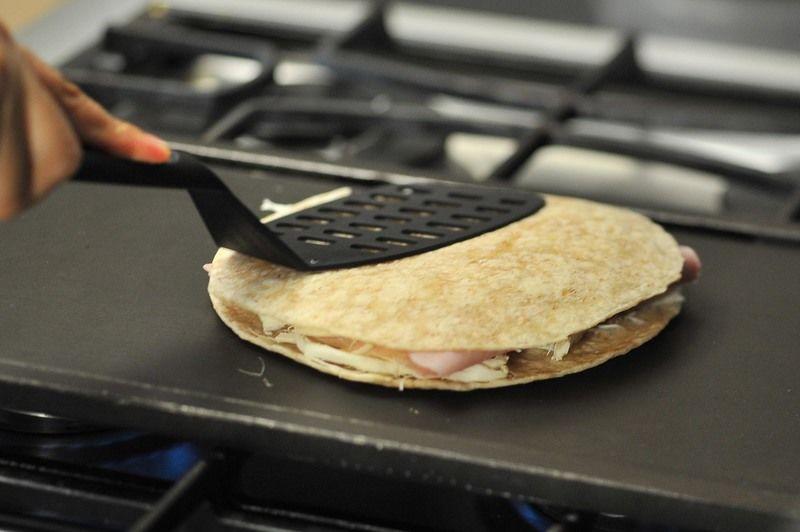 Continuar cociendo un minuto y voltear la tortilla. Cocer hasta que se derrita el queso y voltear una vez más.