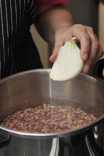 Limpiar los frijoles (retirar las piedritas que pudieran traer) y poner a remoja en un tazón con mucha agua toda la noche para que se empiecen a suavizar. Tirar el agua de remojo y colocar los frijoles junto con el trozo de cebolla y agua limpia en una olla de presión. El agua no debe rebasar la marca de volumen máximo de la olla. Tapar bien la olla, sellar y mover la manija al nivel de cocción para alimentos duros. Encender el fuego alto y en cuanto empiece a silbar, bajar la lumbre y dejar cocer durante 25 minutos. Apagar el fuego y dejar enfriar completamente. Abrir la válvula de escape para dejar escapar el vapor. Abrir y destapar la olla. Si no se cuenta con olla de presión se pueden cocer destapados en una olla normal sobre la estufa durante 3 horas, agregando agua cada vez que sea necesario.