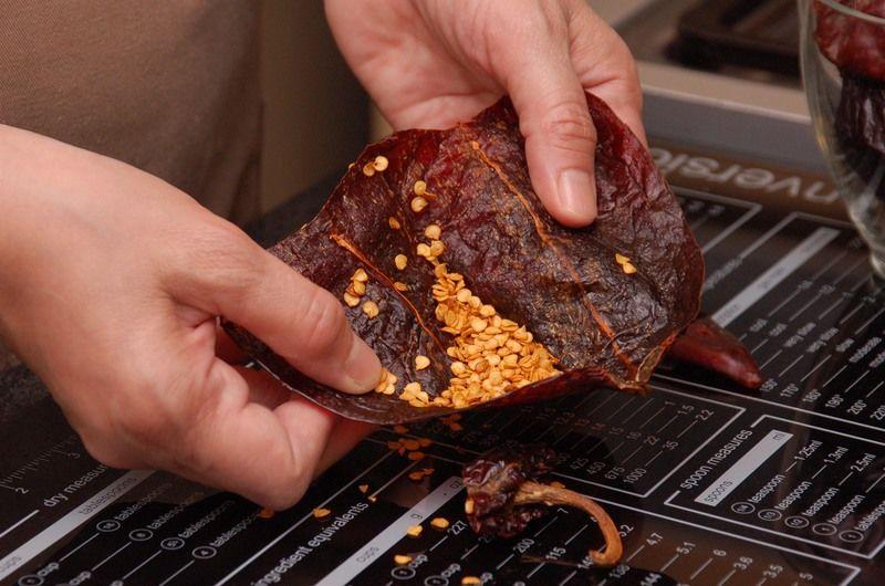 Para preparar la salsa, abrir los chiles anchos y guajillos con una tijera, retirar las semillas, las venas y el rabo.