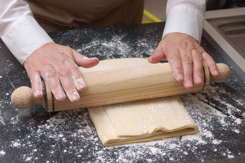 Extender la pasta de hojaldre con un rodillo sobre una mesa enharinada hasta que tenga ½ centímetro de espesor.