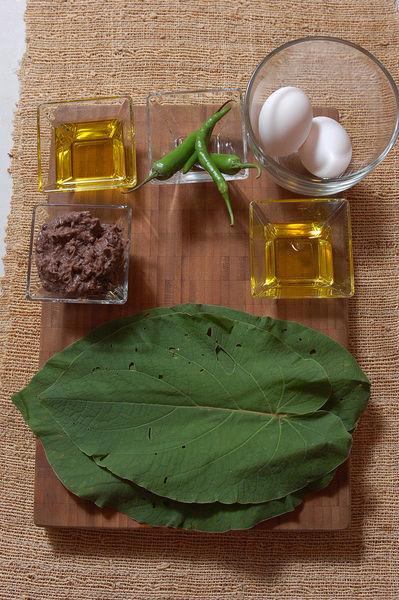 2 cucharadas de aceite de oliva pimienta negra molida al gusto 2 piezas de huevo sal al gusto 3 hojas de hoja santa o acuyo Ingredientes para Acompañar 4 cucharadas de aceite de oliva 2 piezas de chile serrano 1/4 taza de frijoles refritos 2 piezas de chile de árbol