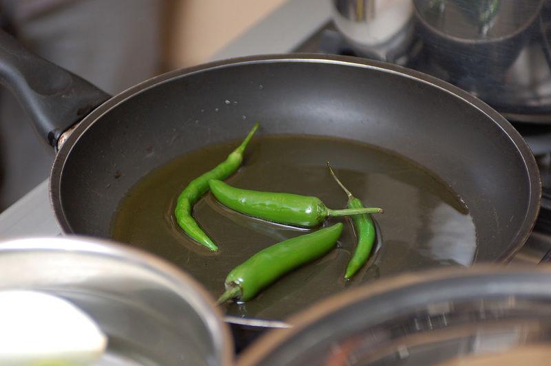 Por otro lado, poner a calentar un poco de aceite en un sartén abierto. Agregar los chiles serranos y los chiles de árbol y sofreír un poco. Apagar el fuego y reservar.