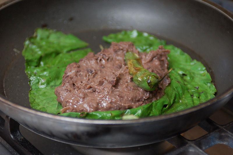 Poner otra hoja barnizada con aceite sobre una sartén como base para los frijoles y los chiles, encender el fuego y calentar.