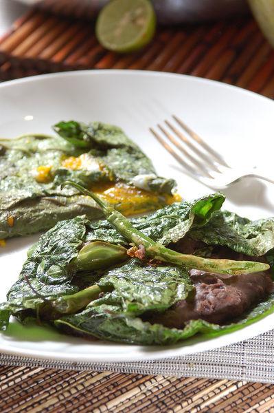Servir los huevos sobre la hoja santa y los frijoles con los chiles también sobre un plato.