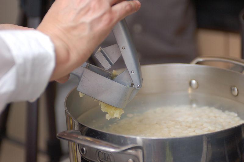 Colocar el maíz en una olla honda con el agua. Pelar los ajos y machacarlos con un machacador de ajos.