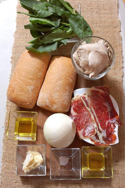 2 cucharadas de aceite de oliva 1/2 manojo de espinaca 1/4 cucharita de sal 50 gramos de queso brie 100 gramos de jamón serrano 1/2 taza de champiñones 4 rebanadas de pan campesino