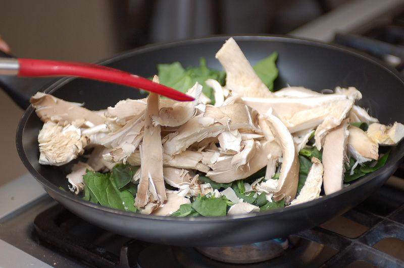 Calentar el aceite de oliva en un sartén abierto, agregar las espinacas picadas y los champiñones fileteados, sazonar con sal y continuar cociendo hasta que las espinacas se reduzcan de tamaño.