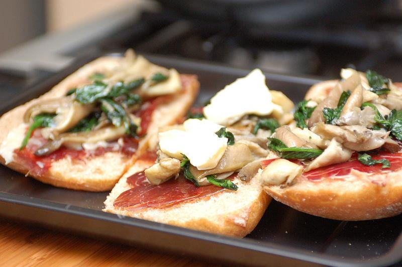 Agregar las rebanadas de queso Brie. Introducir la fuente con los bocadillos al horno precalentado a 400 °F (200°C) durante unos 15 minutos o hasta que el queso se funda sobre el resto de los ingredientes.